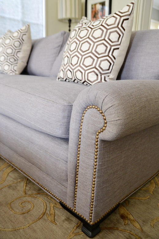 Textured Belgian linen in soft grey with antiqued brass nail heads give this sofa a tailored look which is elegant without feeling too formal. |@D.L. Rhein